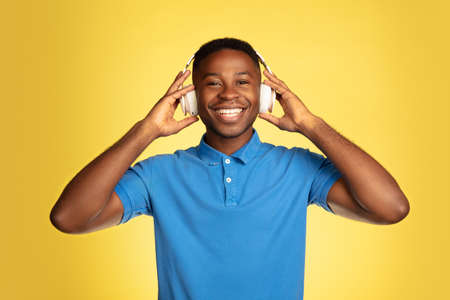 Music in headphones. Young african-american mans portrait isolated on yellow studio background, facial expression. Beautiful male portrait with copyspace. Concept of human emotions, facial expression.