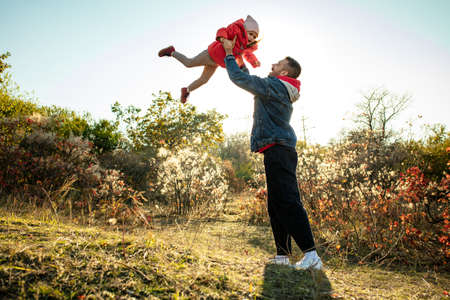Flying high. Happy father and little cute daughter walking down the forest path in autumn sunny day. Family time, togehterness, parenting and happy childhood concept. Weekend with sincere emotions. 版權商用圖片