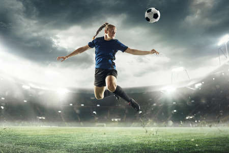 Young female soccer or football player in blue sportswear and boots kicking ball in jump at the stadium in flashlights, spotlights. Concept of professional sport, hobby, motion, movement. 3D render.