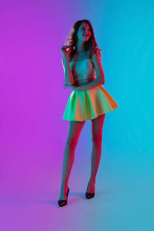 Fashion model. Beautiful seductive girl in fashionable yellow skirt on gradient pink-blue neon studio background. Full-length portrait. Copyspace for ad, design. Summer, fashion, emotions concept. Stock fotó