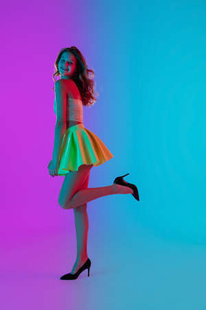 Dancing. Beautiful seductive girl in fashionable yellow skirt on gradient pink-blue neon background. Full-length portrait. Copyspace for ad. Flyer design. Summer, fashion, emotions concept. Stock fotó