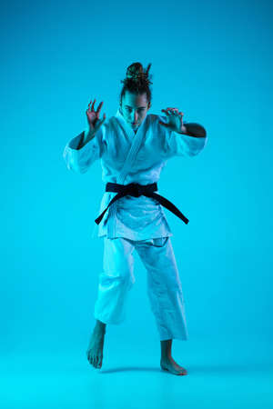Attack. Professional female judoist in white judo kimono practicing and training isolated on blue neoned studio background. Grace of motion and action. Healthy lifestyle, sport concept Banco de Imagens