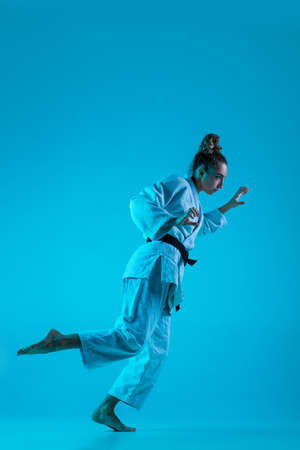 Active training. Professional female judoist in white judo kimono practicing and training isolated on blue neoned studio background. Grace of motion and action. Healthy lifestyle, sport concept