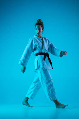 Walking. Professional female judoist in white judo kimono practicing and training isolated on blue neon background. Grace of motion and action. Healthy lifestyle, sport and movement concept.