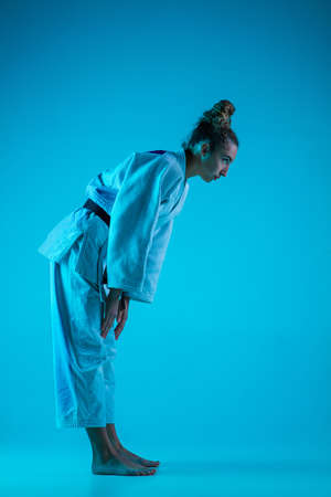 View from side. Professional female judoist in white judo kimono practicing and training isolated on blue neon background. Grace of motion and action. Healthy lifestyle, sport and movement concept.