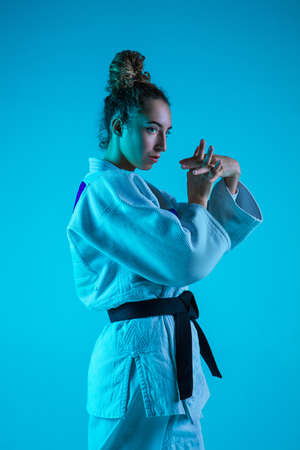 Concentration. Professional female judoist in white judo kimono practicing and training isolated on blue neon background. Grace of motion and action. Healthy lifestyle, sport and movement concept. Banco de Imagens