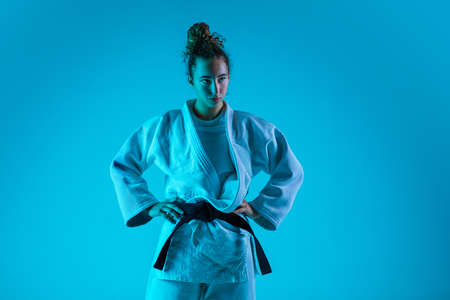 Posing. Professional female judoist in white judo kimono practicing and training isolated on blue neoned studio background. Grace of motion and action. Healthy lifestyle, sport and movement concept
