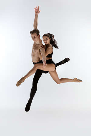 Ballet jump. Young and graceful ballet dancers in black style isolated on white studio background. Art, flexibility, inspiration, lightness of the body concept. Flexible caucasian ballet dancers.