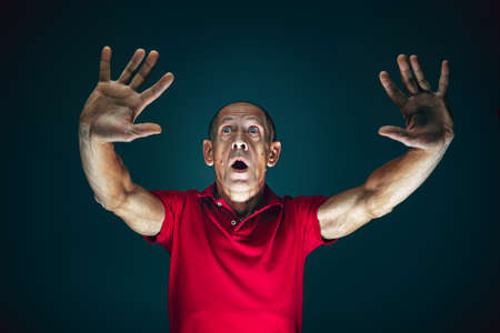 Pushing away from. Portrait of crazy scared and shocked caucasian man isolated on dark background. Copyspace for ad. Bright facial expression, human emotions concept. Watching horror on TV, cinema.