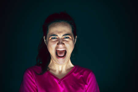 Scream. Portrait of young crazy scared and shocked caucasian woman isolated on dark background. Copyspace for ad. Bright facial expression, human emotions concept. Looking horror on TV, cinema.