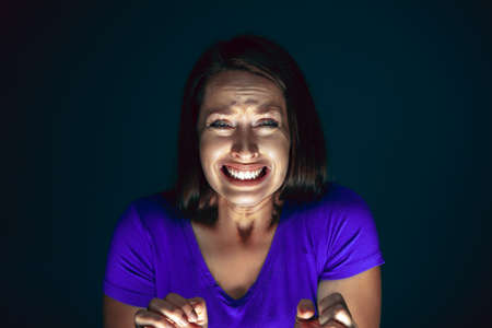 Crying. Portrait of young crazy scared and shocked caucasian woman isolated on dark background. Copyspace for ad. Bright facial expression, human emotions concept. Looking horror on TV, cinema.
