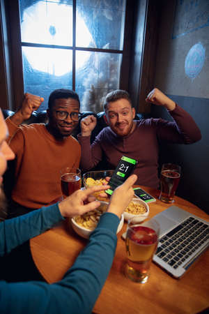 Astonished. Excited fans in bar with beer and mobile app for betting, score on their devices. Screen with match results, emotional friends cheering. Gambling, sport, finance, modern techn concept.
