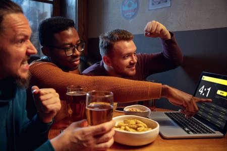 Winners. Excited fans in bar with beer and mobile app for betting, score on their devices. Screen with match results, emotional friends cheering. Gambling, sport, finance, modern techn concept.