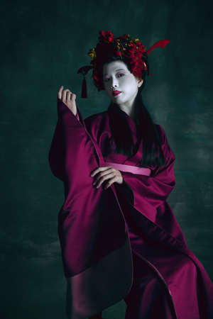 Blossom youth. Young japanese woman as geisha isolated on dark green background. Retro style, comparison of eras concept. Beautiful female model like bright historical character, old-fashioned. 免版税图像