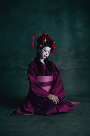 Humble. Young japanese woman as geisha isolated on dark green background. Retro style, comparison of eras concept. Beautiful female model like bright historical character, old-fashioned. 免版税图像