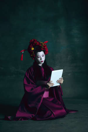 Scrolling tablet. Young japanese woman as geisha isolated on dark green background. Retro style, comparison of eras concept. Beautiful female model like bright historical character, old-fashioned.