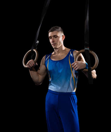 Strong. Muscular male gymnast training in gym, flexible and active. Caucasian fit guy, athlete in blue sportswear doing exercises for strength, balance. Movement, action, motion, dynamic concept.