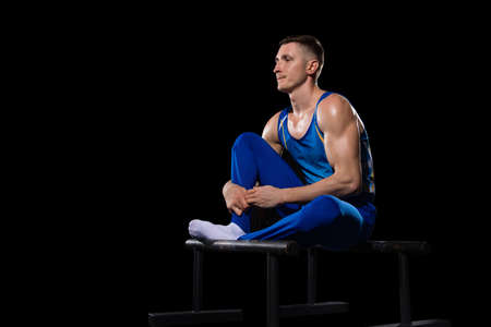Inspired. Muscular male gymnast training in gym, flexible and active. Caucasian fit guy, athlete in blue sportswear doing exercises for strength, balance. Movement, action, motion, dynamic concept.