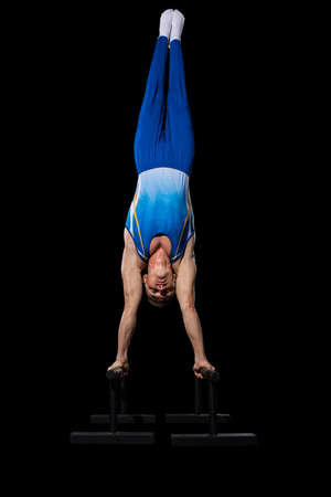 Staying up. Muscular male gymnast training in gym, flexible and active. Caucasian fit guy, athlete in blue sportswear doing exercises for strength, balance. Movement, action, motion, dynamic concept. Imagens