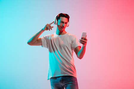 Listening to music, dancing. Young caucasian mans portrait on gradient blue-pink studio background in neon. Concept of youth, human emotions, facial expression, sales, ad. Half length, copyspace.