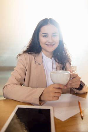 Coffee break. Young woman working in videoconference with co-workers at office. Online business, education during coronavirus and quarantine. Work, finance, modern tech concept. View from the screen.