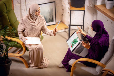 Tech. Happy and young two muslim women at home during lesson, sitting in armchairs, online education. Culture, traditions, modern people. Watching at device screen, shopping or talking. Reklamní fotografie