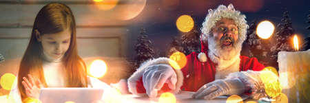Miracle. Happy caucasian little girl during video call with Santa Claus on the laptops screen and home devices, looks dreamful. Celebration or ad flyer with copyspace. New 2021 Year meeting.