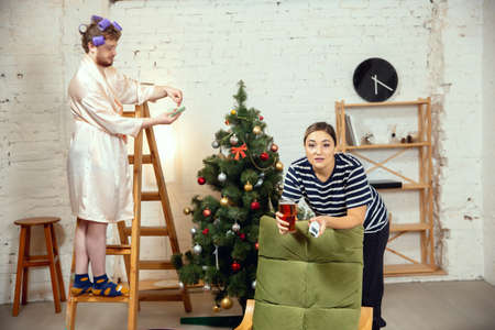Gender stereotypes. Wife and husband doing things unusual for their genders in social meanings, sense. Man decorating Christmas tree for New Year celebration, woman drinking beer bored, watching TV. Foto de archivo