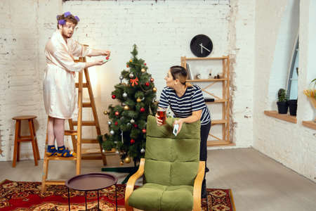 Gender stereotypes. Wife and husband doing things unusual for their genders in social meanings, sense. Man decorating Christmas tree for New Year celebration, woman drinking beer bored, watching TV.