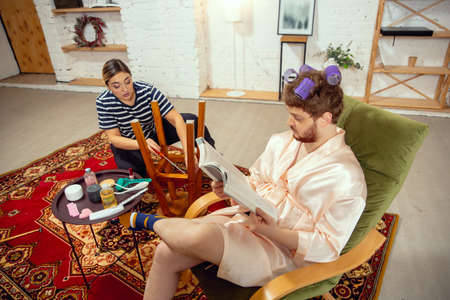 Gender stereotypes. Wife and husband doing things unusual for their genders in social meanings, sense. Man has a beauty day, doing hairstyle, reading magazine while woman repairing table, chairs.