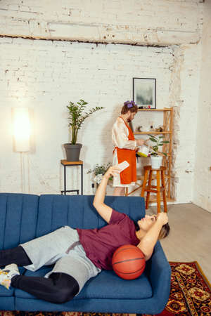 Gender stereotypes. Wife and husband doing things unusual for their genders in social meanings, sense. Man cooking dinner while woman training in basketball with the ball in living room.