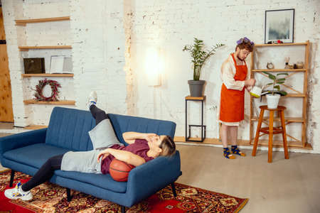 Gender stereotypes. Wife and husband doing things unusual for their genders in social meanings, sense. Man cooking dinner while woman training in basketball with the ball in living room. Foto de archivo