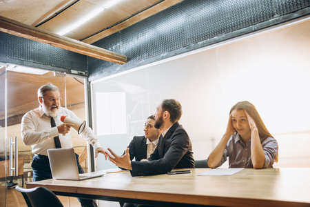 Discuss. Angry boss with megaphone screaming at employees in office, scared and annoyed colleagues listening at the table stressed out. Funny meeting, business, office concept. Screaming mad. Stock Photo