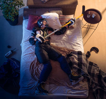 Always ready. Top view of young professional hockey player sleeping at his bedroom in sportwear with equipment. Loving his sport, workaholic, playing match even if resting. Action, motion, humor. Stock fotó