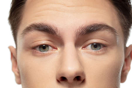 Eyes calm. Close up face of young man on white studio background. Caucasian attractive male model. Concept of fashion and beauty, self-care, body and skin care. Handsome boy with well-kept skin.