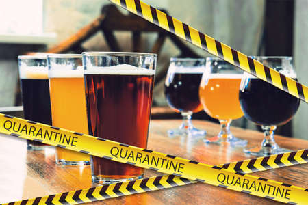 Glasses of different types of beer at bar with bounding tapes Lockdown, Coronavirus, Quarantine, Warning - closing bars, restaurants and nightclubs during pandemic. Lowed social life, ban of group meeting.