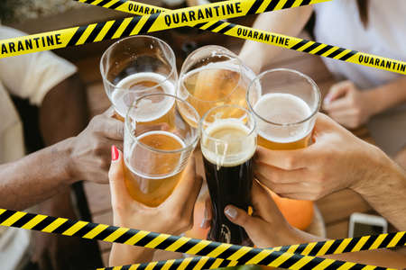 Close up hands clinking glasses with beer bounding tapes Lockdown, Coronavirus, Quarantine, Warning - closing bars, restaurants and nightclubs during pandemic. Lowed social life, ban of group meeting.