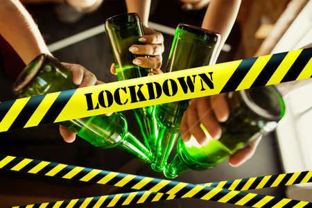Close up hands clinking bottles with beer bounding tapes Lockdown, Coronavirus, Quarantine, Warning - closing bars, restaurants and nightclubs during pandemic. Lowed social life, ban of group meeting.