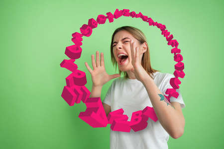 Woman shouting, screaming angry, highly tensioned on green studio background. Sales, offer, business, cheering fun concept. Stream of letters flying from the inside of rupor. Copyspace for ad.