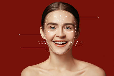 Beautiful female face with lifting up arrows isolated on red background. Concept of bodycare, cosmetics, skincare, correction surgery, beauty and perfect skin. Flyer for your ad. Antiaging. Foto de archivo