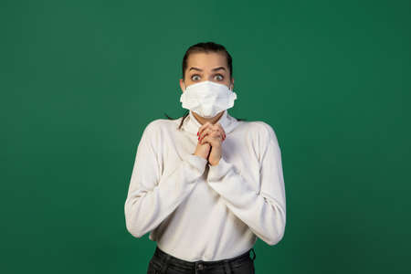 Shocked. Woman in protective face mask isolated on green studio background. New rules  spreading prevention. Copyspace for ad. Pandemic, healthcare and medicine
