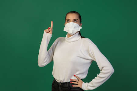 Pointing. Woman in protective face mask isolated on green studio background.