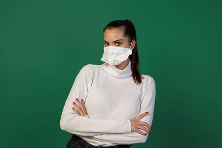 Calm. Woman in protective face mask isolated on green studio background.