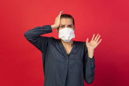 Shocked, scared. Woman in protective face mask isolated on red studio background.