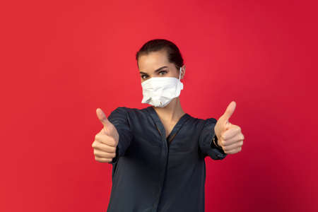 Thumbs up. Woman in protective face mask isolated on red studio background.