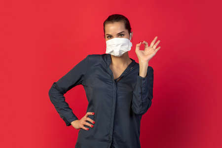 Nice sign. Woman in protective face mask isolated on red studio background. Stockfoto