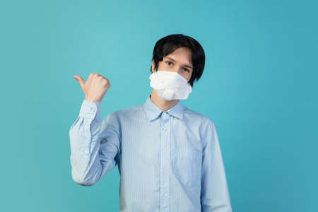 Pointing. Man in protective face mask isolated on blue studio background.