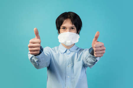 Thumbs up. Man in protective face mask isolated on blue studio background.
