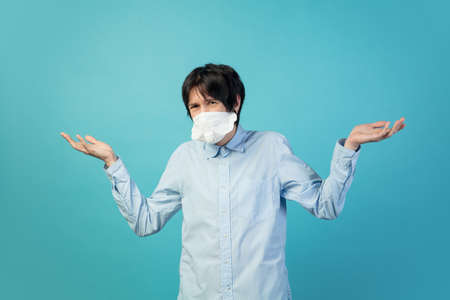 Disappointed. Man in protective face mask isolated on blue studio background.
