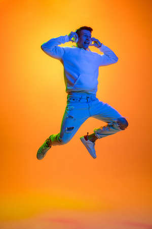 Flying. Caucasian mans portrait isolated on yellow studio background in mixed neon light. Listening music in headphones. Concept of human emotions, facial expression, sales, ad, fashion. Copyspace.